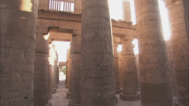 the sun shines on pillars covered with hieroglyphs in an ancient temple. - temples of karnak stock videos and b-roll footage