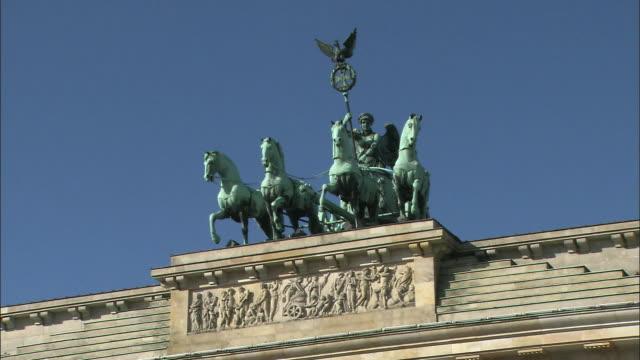 The sun shines on the Quadriga Statue atop the Brandenburg Gate.
