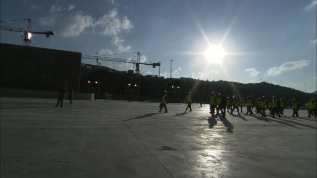 the sun shines over a construction crew walking through a military base. - army stock videos & royalty-free footage