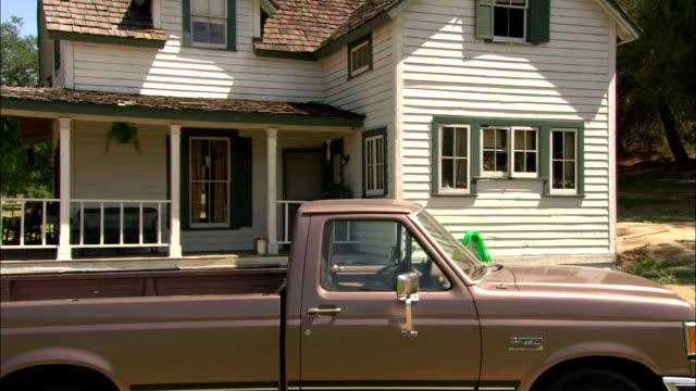 the sun shines over a house with a wrap-around porch and a pickup parked in the driveway. - zweistöckiges wohnhaus stock-videos und b-roll-filmmaterial