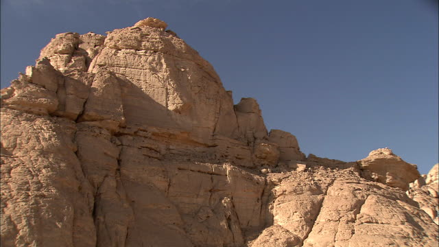 the sun shines over a large outcropping in the desert. - butte rocky outcrop stock videos & royalty-free footage