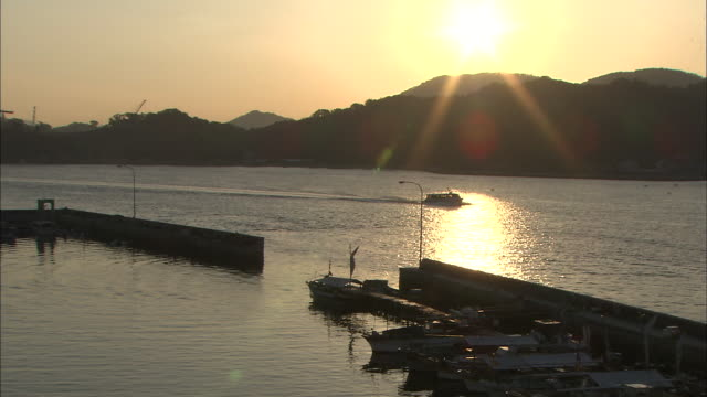 the sun shines over a mountain as a boat travels on the water near a harbor. - onomichi hiroshima stock videos and b-roll footage