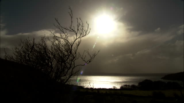 the sun shines over cloud covered water. - cespuglio video stock e b–roll