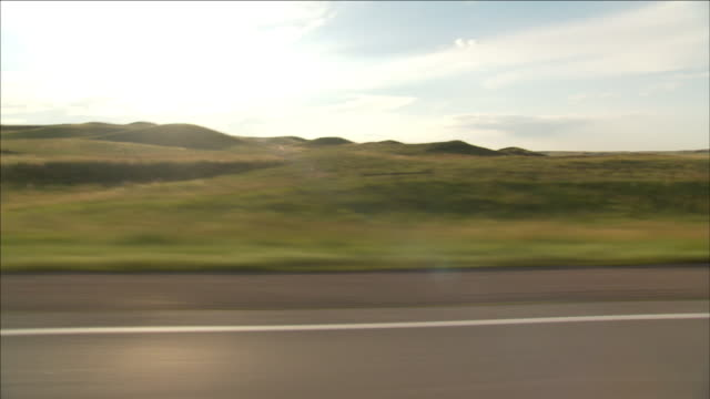 the sun shines over rolling hills and a rural highway. - hügellandschaft stock-videos und b-roll-filmmaterial