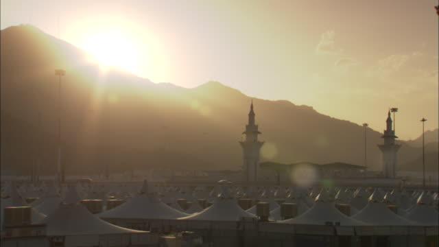 the sun shines over the beautiful neighborhood of mina in mecca, saudi arabia. - tent stock videos and b-roll footage