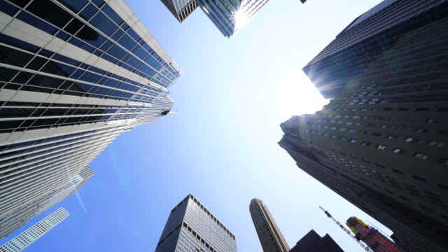 the sun shines over the park avenue skyscrapers at midtown manhattan new york city. - 真下からの眺め点の映像素材/bロール