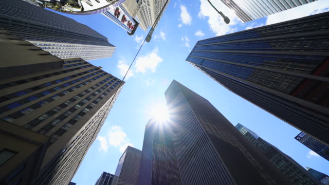 the sun shines over the sixth avenue skyscrapers at midtown manhattan new york city. - 真下からの眺め点の映像素材/bロール