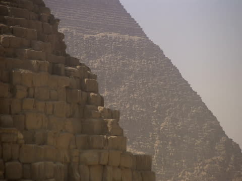 the sun shines over the thousands of stone blocks making up one of the great pyramids. - stone material stock videos and b-roll footage