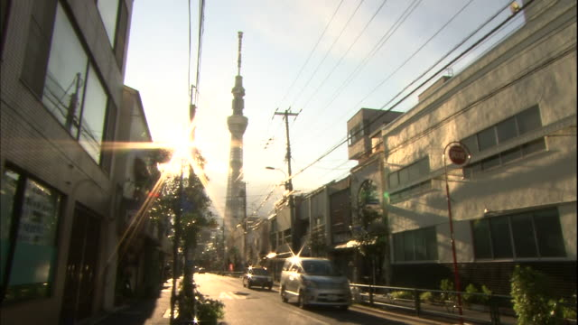 The sun shines over the Tokyo Skytree and traffic traveling along a street.