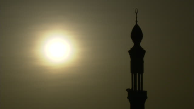 the sun shines through a hazy sky over a minaret. - minaret bildbanksvideor och videomaterial från bakom kulisserna