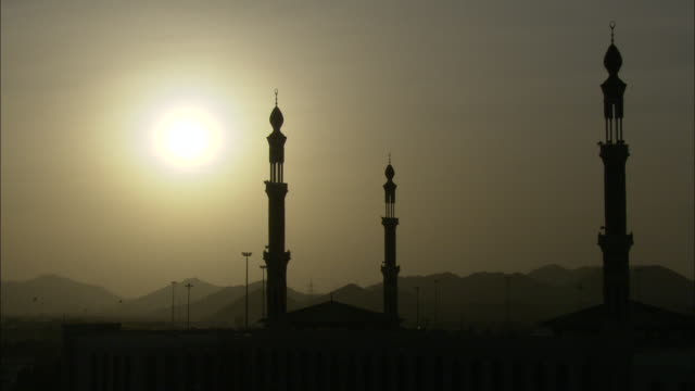 vídeos de stock e filmes b-roll de the sun shines through a hazy sky over a mosque with minarets. - minarete