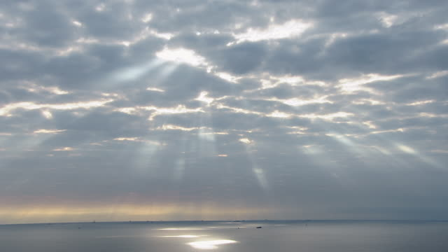The sun shines through clouds onto ships scattered on the ocean.