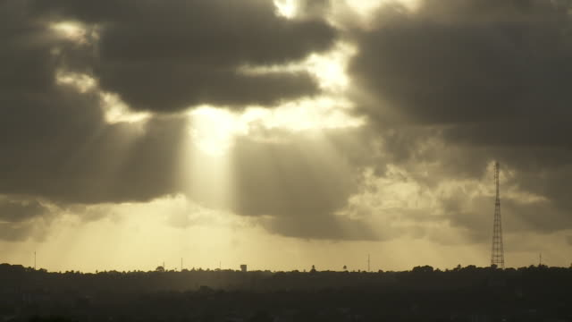 the sun shines through dark clouds over a radio antenna. - recife stock videos and b-roll footage
