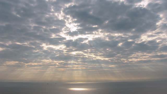 The sun shines through golden clouds onto the ocean.