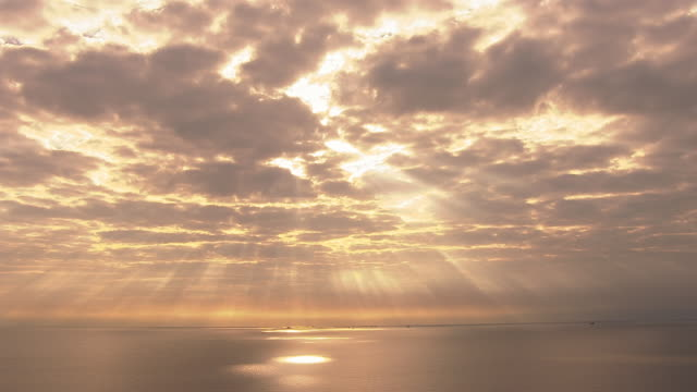 the sun shines through golden clouds onto the ocean. - 太陽光線点の映像素材/bロール