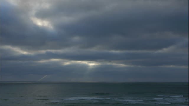 The sun shines through gray clouds as they pass near Cannon Beach.