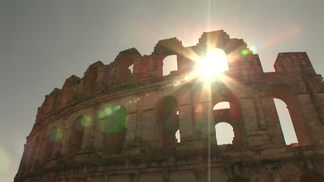 the sun shines through the arch of an ancient roman amphitheater. - amphitheatre stock videos & royalty-free footage