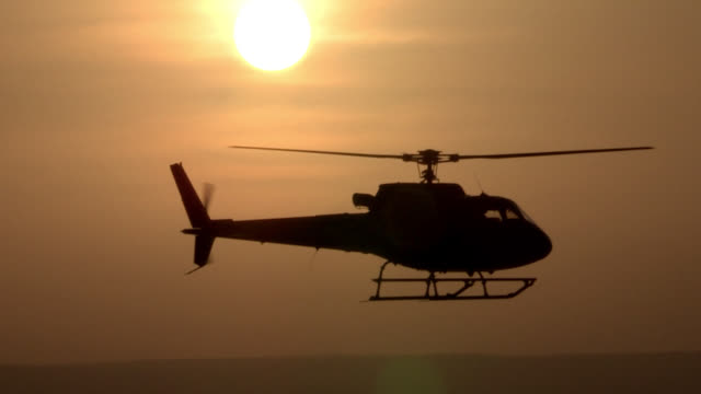 the sun silhouettes a hovering helicopter. - helicopter rotors stock videos and b-roll footage