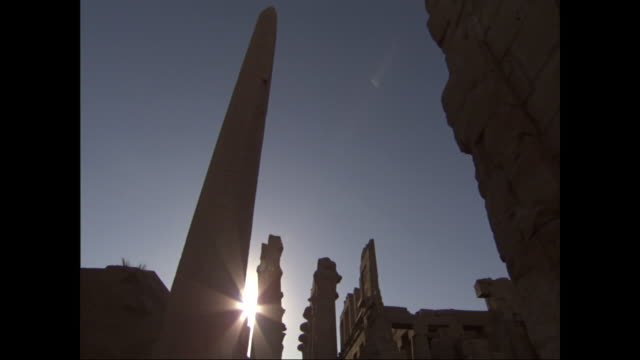 the sun silhouettes a stone obelisk and ancient egyptian ruins. - obelisk stock-videos und b-roll-filmmaterial