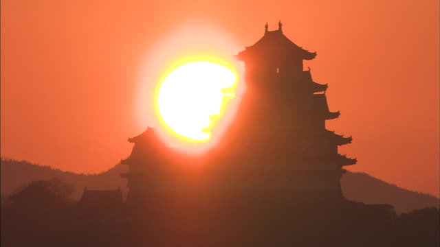 The sun silhouettes Himeji Castle in Japan.