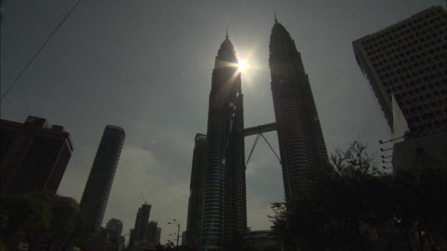 the sun silhouettes kuala lumpur's petronas twin towers. - petronas twin towers stock-videos und b-roll-filmmaterial