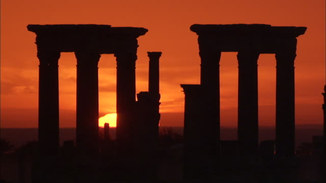 The sun sinks behind stone ruins in the ancient city of Palmyra. Available in HD
