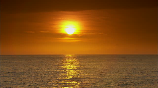 The sun slowly sets over an ocean.