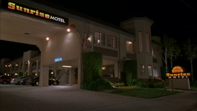 the sunrise motel is illuminated at night. - motel stock videos and b-roll footage