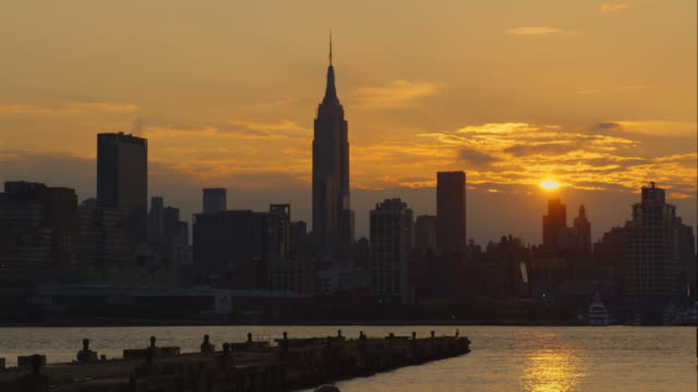 The sunrises over a a golden sky and the the Manhattan Skyline