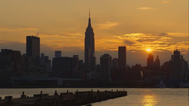 stockvideo's en b-roll-footage met the sunrises over a a golden sky and the the manhattan skyline - stilstaande camera