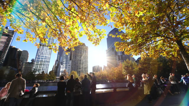 The sunset illuminates autumnal leaves and people from through the interval of the buildings at 9/11 Memorial