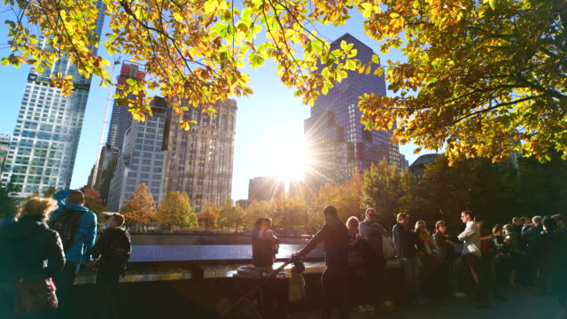 the sunset illuminates autumnal leaves and people from through the interval of the buildings at 9/11 memorial - memorial stock videos & royalty-free footage