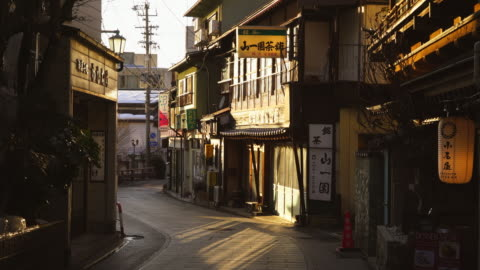 the sunset illuminates the japanese style houses along the street at yudanaka onsen (yudanaka hot spring) yamanouchi-machi, nagano japan on feb. 18 2019. - 路地点の映像素材/bロール