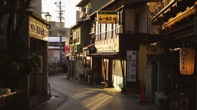 the sunset illuminates the japanese style houses along the street at yudanaka onsen (yudanaka hot spring) yamanouchi-machi, nagano japan on feb. 18 2019. - 温泉点の映像素材/bロール