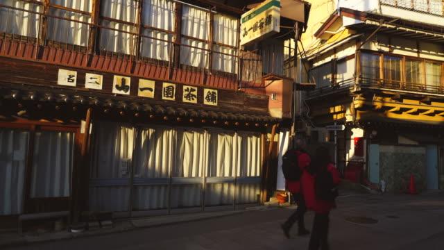 the sunset illuminates the japanese style houses along the street at shibu onsen (shibu hot spring) yamanouchi-machi, nagano japan on feb. 18 2019. - joshinetsu kogen national park stock videos and b-roll footage