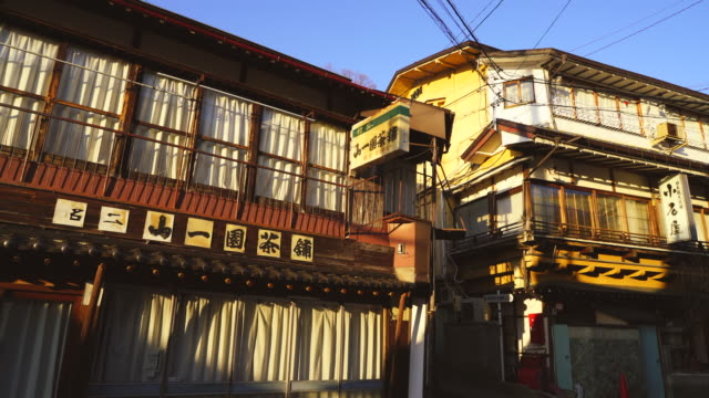The sunset illuminates the Japanese Style Houses along the street at Shibu Onsen (Shibu Hot Spring) Yamanouchi-machi, Nagano Japan on Feb. 18 2019.
