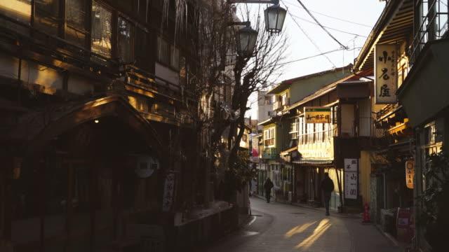 the sunset illuminates the japanese style houses and ryokan (traditionaljapaneseinn) stand along the street at shibu onsen (shibu hot spring) yamanouchi-machi, nagano japan on feb. 17 2019. - ryokan stock videos and b-roll footage