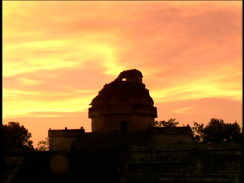 the sunset sky glows behind an ancient mayan observatory. - mayan stock videos & royalty-free footage