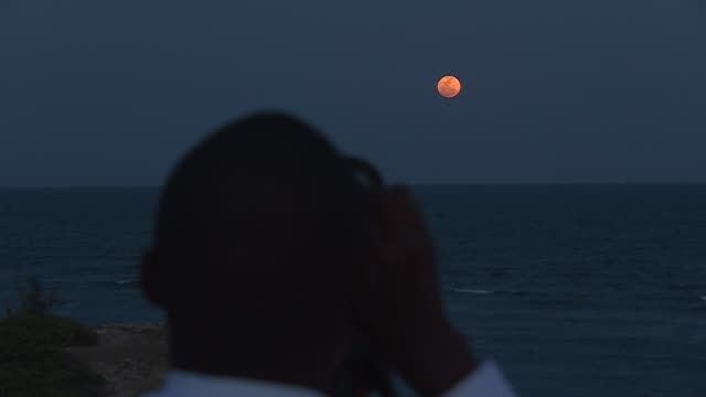 the supermoon rises over dar es salaam tanzania as the sun sets - supermoon stock videos & royalty-free footage