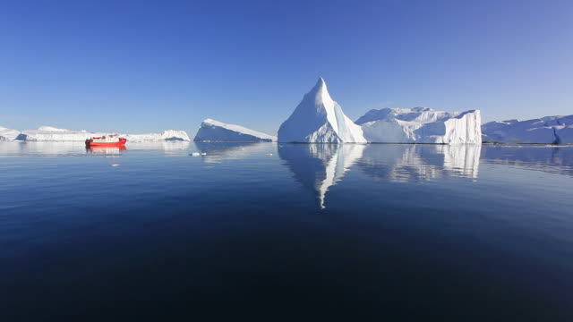 The surface of the ocean reflects icebergs.