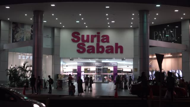The Suria Sabah shopping mall stands illuminated at dusk in Kota Kinabalu Sabah Malaysia on Saturday July 29 Shoppers stand outside the Suria Sabah...