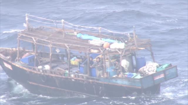 [ shot nov29th ] as the suspected nkorean boat [ shot dec4th ] gv investigators leaving for the island matsumaekojima as wide shot of the island... - suspicion stock-videos und b-roll-filmmaterial