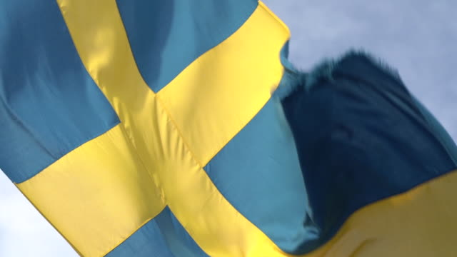 the swedish national flag waving in the air behind a cruise ship - swedish flag stock videos and b-roll footage