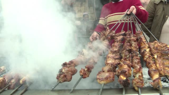 the sweet aroma of mutton smoke drifts through a maze of crumbling alleyways a barbecue tang that for decades has lured meat eaters from across... - peshawar stock videos & royalty-free footage