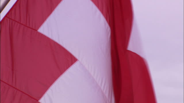 The Swiss flag flutters in a breeze.