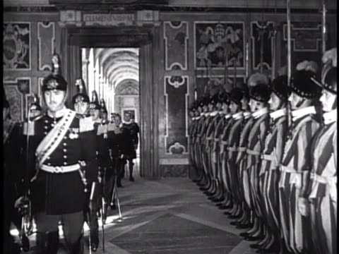 the swiss guard standing at attention as visitors in uniform walk down hallway cardinal secretary of state the roman curia luigi maglione seated at... - 近衛兵点の映像素材/bロール