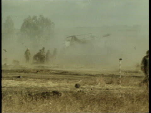 the syria collection 1; 8.10.73 yom kippur war: gerald seymour into camera; israeli guns firing in golan heights; tanks and apcs on road; jet flying... - ヨムキプール点の映像素材/bロール