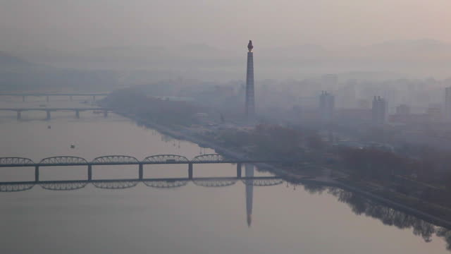 the taedong river flows past the juche tower in pyongyang. - pyongyang stock videos and b-roll footage