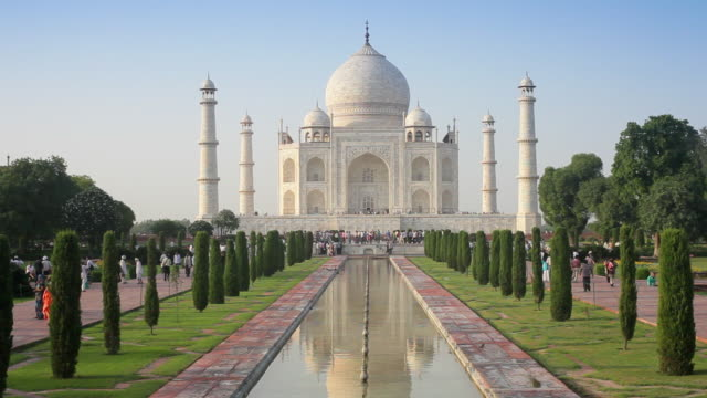 the taj mahal casts a reflection on the surface of a pool. - taj mahal stock videos and b-roll footage