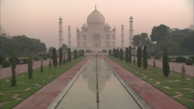 the taj mahal rises above a reflecting pool. - mughal empire stock videos and b-roll footage